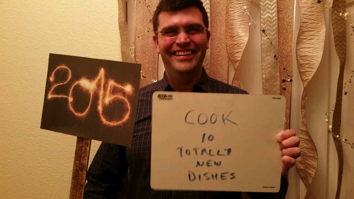 "Greg Holding Sign Saying: ""Cook 10 Totally New Dishes"""